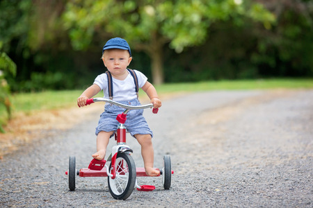 Cute toddler boy, playing with tricycle in backyard, summertime