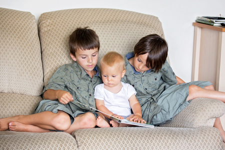 Three boys, siblings, sitting on a sofa and reading a book in living room, summertime