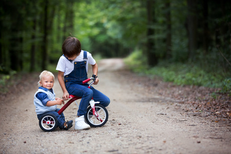 Cute toddler child and his older brothers, boys, siblings, playing with tricycle in park, having fun Stock Photo