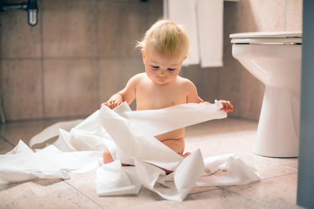 Toddler baby boy, child ripping up with toilet paper in bathroom 写真素材 - 108209681