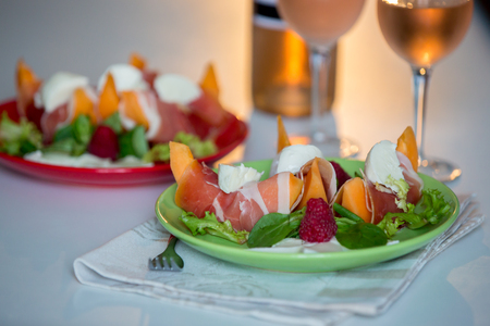 Melon, mozzarella and prosciutto  and fruits salad with glass of wine 스톡 콘텐츠