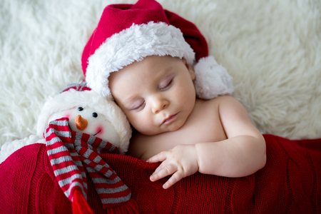Little sleeping newborn baby boy, wearing Santa hat, holding toy Stockfoto