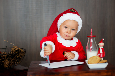 Sweet toddler child, boy, writing letter to santa at home, eating cookies and drinking milk