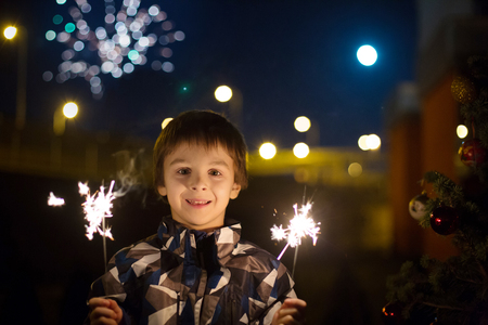 Preschool children, holding sparkler, celebrating new years eve outdoors, watching fireworks Archivio Fotografico - 108209789