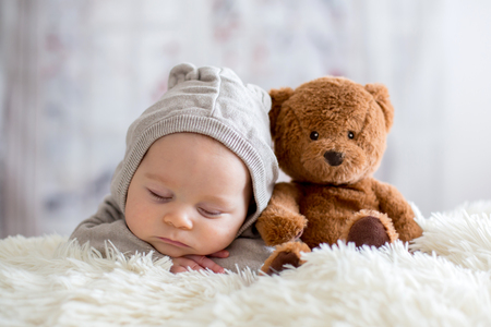 Sweet baby boy in bear overall, sleeping in bed with teddy bear stuffed toys, winter landscape behind him 免版税图像