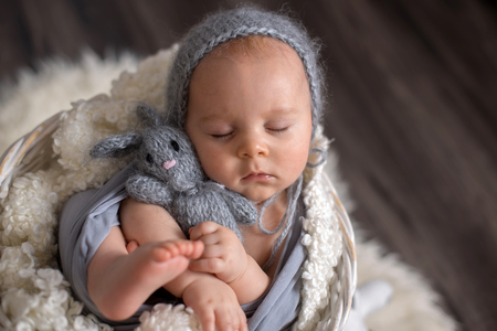 Sweet baby boy in basket, holding and hugging teddy bear, peacefully sleeping wrapped in grey scarf Stock Photo