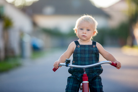 Cute toddler child, boy, playing with tricycle on the street, kid riding bike on sunset