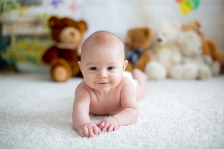 Little baby boy playing at home with soft teddy bear toys, lying down Stock Photo