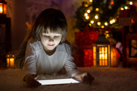 Cute boy, lying on the floor, playing on tablet at night, christmas time, waiting for Santa Claus