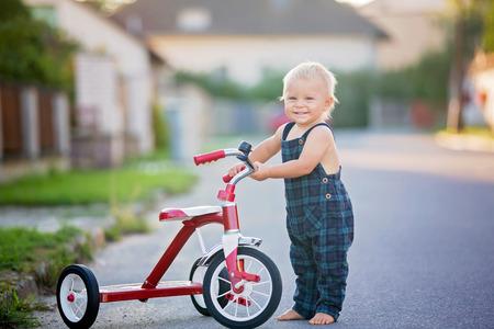 Bambino sveglio del bambino, ragazzo, che gioca con il triciclo sulla strada, bicicletta di guida del bambino sul tramonto
