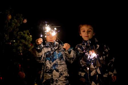 Preschool children, holding sparkler, celebrating new years eve outdoors, watching fireworks