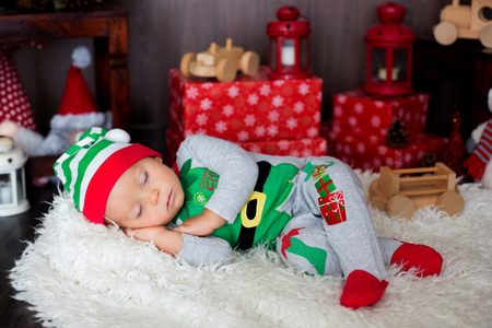 Sweet toddler child, boy, sleeping with lots of toys, dressed like an elf, cristmas decoration around him