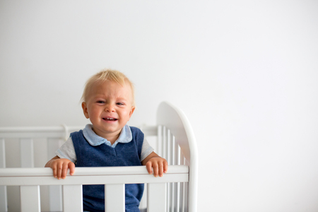 Sad little baby boy, nicely dressed, feeling unhappy in baby cot, looking through bars