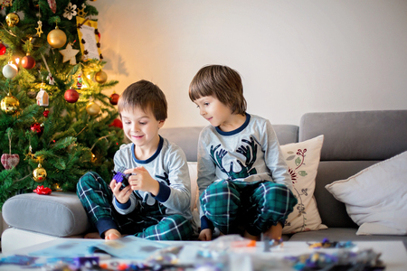 Preschool children, boy brothers, playing together with colorful blocks, building different toys on Christmas day, after opening presents at home Stock Photo