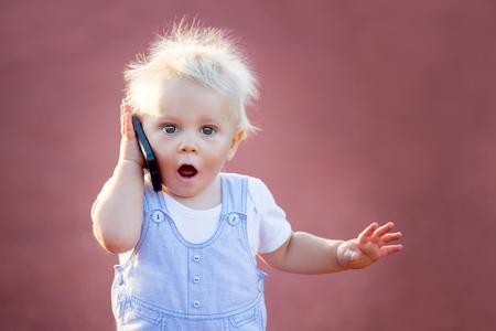 Ładny chłopczyk bawi się telefonem komórkowym w parku, technologie cyfrowe w rękach dziecka. Portret malucha ze smartfonem