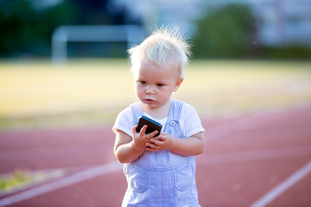 Cute baby boy playing with mobile phone in the park, digital technologies in the hands of a child. Portrait of toddler with smartphone