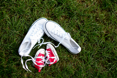 Red baby toddlers sneakers and white woman sneakers on the grass, lased together Stock Photo - 109852914