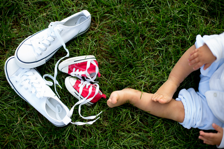 Red baby toddlers sneakers and white woman sneakers on the grass with little baby feet Stock Photo - 109853148