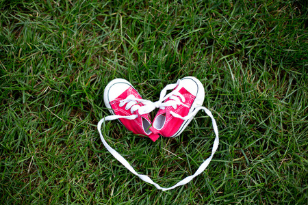 Red baby toddlers sneakers on the grass