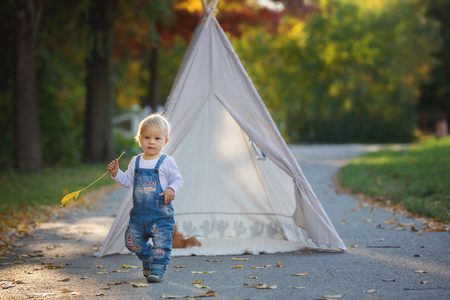 Children, sitting in a tent teepee, holding teddy bear toy with a nature autumn background in the park, imagination or happiness concept