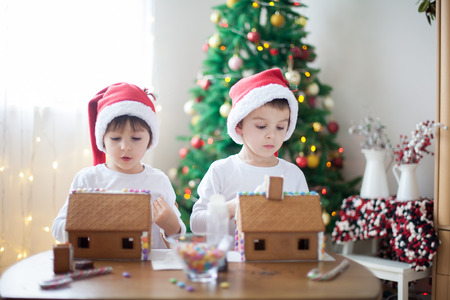Two sweet boys, brothers, making gingerbread cookies house, decorating at home in front of the Christmas tree, child playing and enjoying, Christmas concept Stock Photo