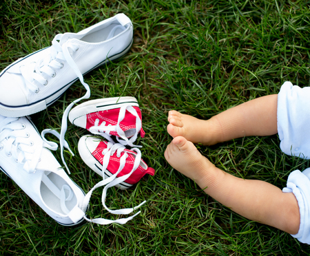 Red baby toddlers sneakers and white woman sneakers on the grass with little baby feet Stock Photo - 109853390