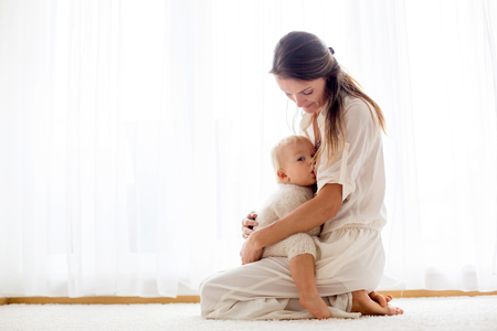 Young mother breastfeeding her toddler baby boy at home Stockfoto