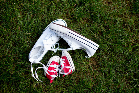 Red baby toddlers sneakers and white woman sneakers on the grass, lased together Stock Photo - 109853392