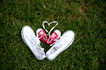 Red baby toddlers sneakers and white woman sneakers on the grass, lased together Stock Photo - 109853393