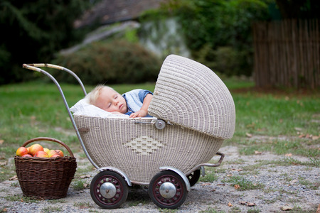 Little newborn baby boy, sleeping in old retro stroller in forest, autumn time. Posed baby in retro pram, baby sleeping, vintage stroller Banco de Imagens