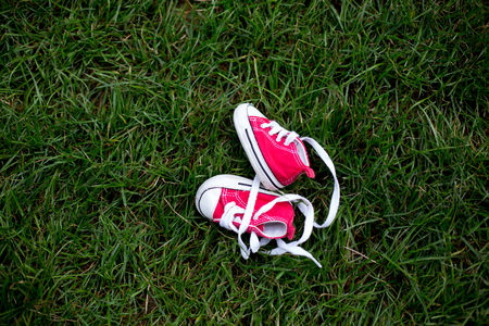 Red baby toddlers sneakers on the grass Stock Photo - 109853634