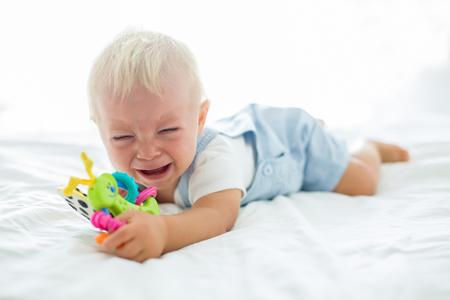 Niño pequeño, jugando con el maniquí, llorando descontento por el chupete en el dormitorio de los niños