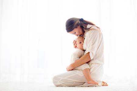 Young mother breastfeeding her toddler baby boy at home Stock Photo