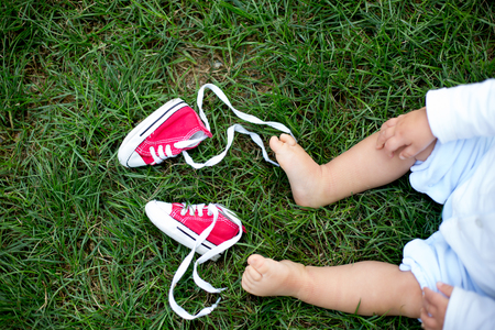 Red baby toddlers sneakers and white woman sneakers on the grass with little baby feet Stock Photo