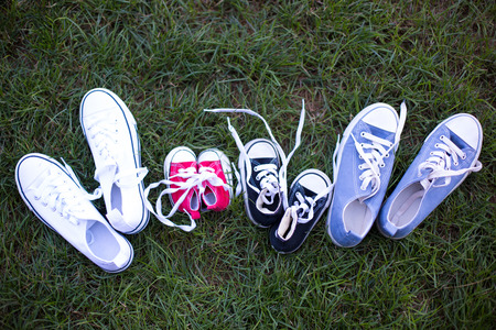 Four different colors pair of sneakers, shoes for the whole family lying on the grass