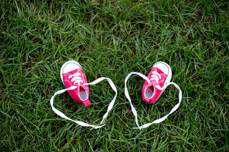 Red baby toddlers sneakers on the grass Stock Photo - 109854374
