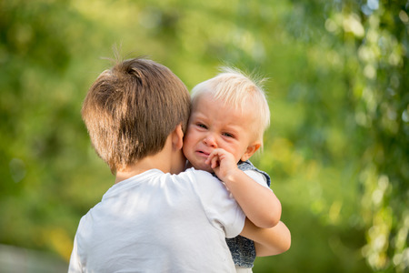 Little toddler baby boy, crying, older brother carrying him in the park, baby looking at camera