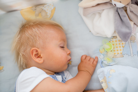 Little baby boy, sleeps in baby bed with pacifier nearby Stock Photo