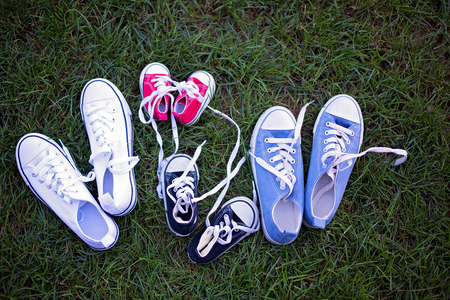 Four different colors pair of sneakers, shoes for the whole family lying on the grass Stock Photo - 109854562