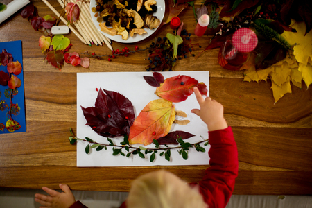 Children, applying leaves using glue, scissors, and paint, while doing arts and crafts in school, autumntime 免版税图像