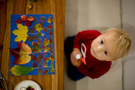 Children, applying leaves using glue, scissors, and paint, while doing arts and crafts in school, autumntime 写真素材