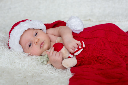 Little newborn baby boy, wearing Santa hat and pants, holding toy, curiously smiling at camera Stockfoto