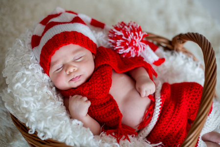 Little sleeping newborn baby boy, wearing Santa hat and pants, holding toy Stockfoto