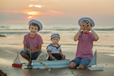 Sailor baby boy, cute child, playing on the beach with wooden boat, fishes and fishing rod on sunset by the ocean