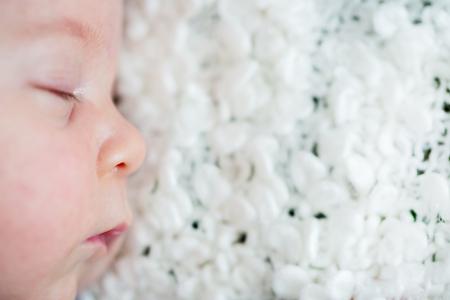 Beautiful newborn baby boy, sleeping with little toy Imagens