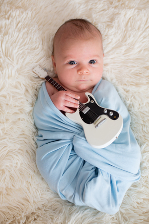 Newborn baby boy, wrapped in blue scarf, holding a little guitar and smiling 스톡 콘텐츠