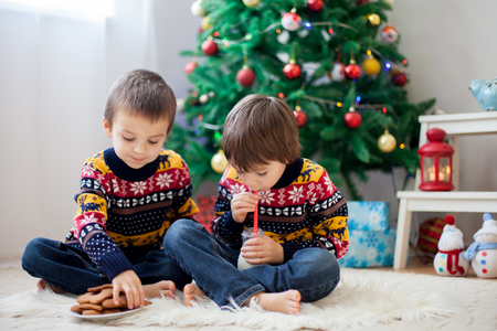 Two adorable children, boy brothers, eating cookies and drinking milk at home, Christmas decoration behind then, kids having fun. Christmas concept 版權商用圖片