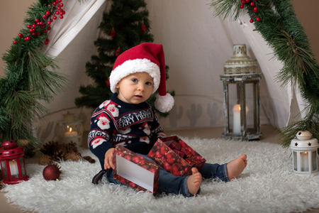 Adorable toddler child, boy, having his christmas portrait taken in decorated room with teepee, snowman and other chirstmas decoration, dressed festivly for Christmas and wearing santa hat