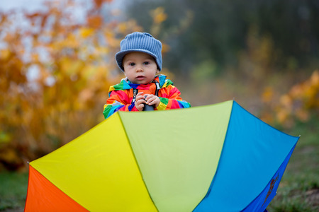 Sweet funny child with rainboy coat and multicolored umbrella jumping on puddles iand playing outdoors after rain Imagens