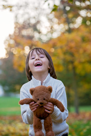 Cute preschool child, boy, holding little brown teddy bear in the park, autumn on sunset, back light. Selective focus